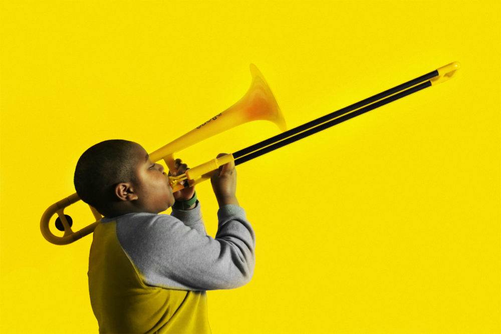 Boy playing yellow trombone